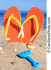 Flip-flops. - Orange flip-flops in sand on the beach in...