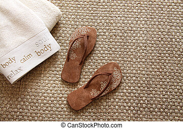 Flip flops with towels on seagrass rug