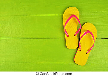 Flip Flops Yellow on green wooden background