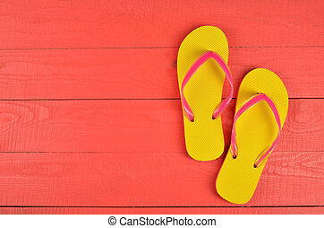 Flip Flops Yellow on red wooden background