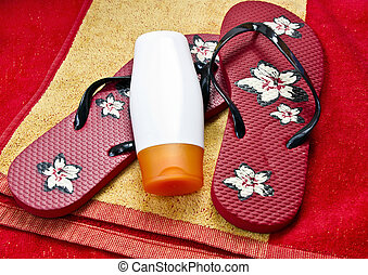 Flipflop and sunscreen on a beach towel with amazing colors
