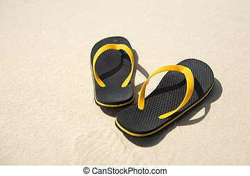 Image of pair of yellow and black flipflops on sandy beach