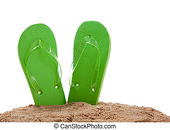 Green flipflops in sand on a white background with copy space