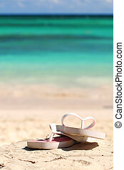 Flipflops on a sandy ocean beach - vacation concept