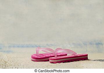 pair of pink flip flops in the sand
