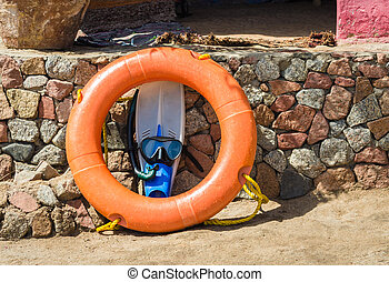 flippers with swimming mask and an orange life preserver against a stone wall in Egypt