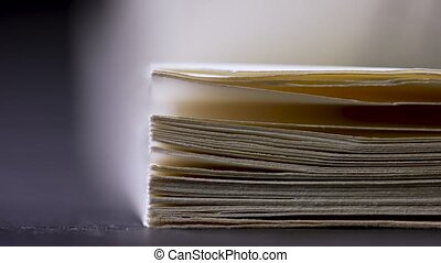 Flipping blurry pages of a book in the studio on a black background. Slow motion. Close up.