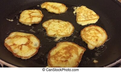 Flipping latkes pancakes fried in oil and butter - Shot of...