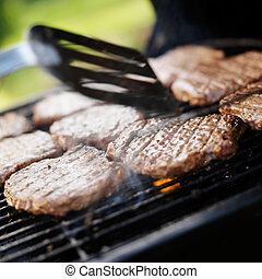 flipping over burgers on grill
