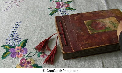 Red color antique photo album on the table covered with vintage tablecloth opened and pages flipping fast.