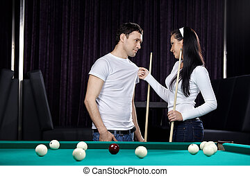 Flirtation - Young attractive couple near to a billiard...