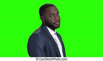 Flirtatious afro-american businessman on green screen. Portrait of dark-skinned flirting man on chroma key background. Self-assertive macho-man.