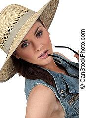 Flirtatious brunette wearing straw hat