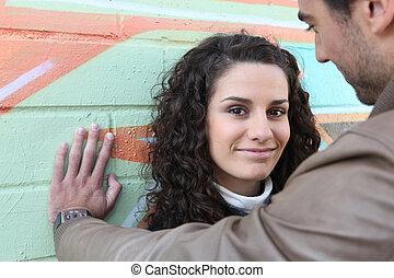 Flirtatious couple stood by wall