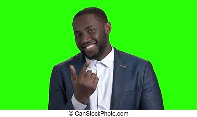 Flirtatious dark-skinned man on green screen. Attractive afro american is man flirting and inviting somebody with finger on chroma key background. Handsome smiling macho-man.