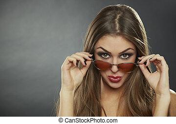 Flirtatious woman wearing sunglasses