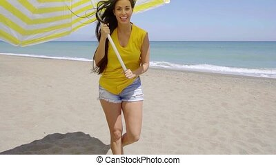 Flirtatious young woman in a yellow summer top holding a yellow and white striped beach umbrella while smiling seductively at the camera