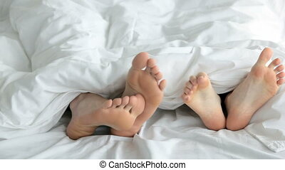 Tilt up of young lovers flirting and kissing in bed