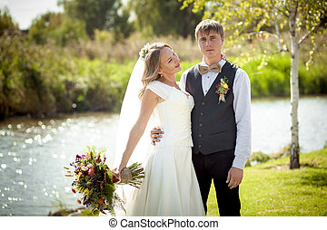flirting bride with groom near pond