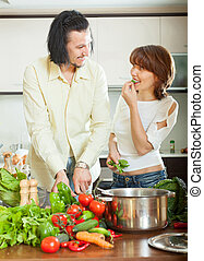 Flirting couple  with vegetables in  kitchen