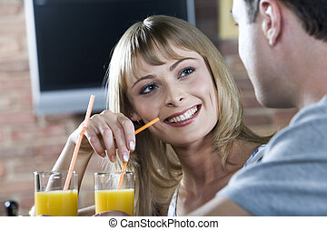 Flirting in the bar - Smiling cute blond woman listening to...