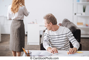 Flirting mature worker looking at young woman body at work