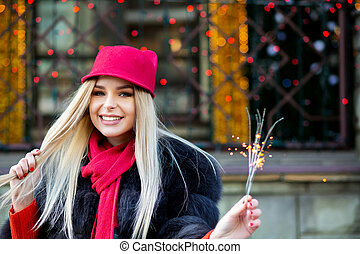Flirty blonde model celebrating New Year with sparklers at the blurred city lights. Space for text