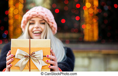 Flirty blonde model wearing fur coat and knitted cap pulls a gift box to you. Space for text