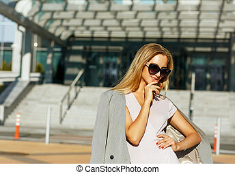 Flirty blonde woman in stylish glasses posing at the avenue in sunny day. Space for text