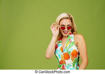 Flirty blonde woman peeking from under her sunglasses