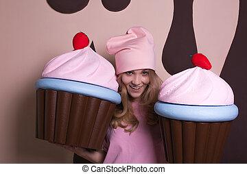 Flirty blonde woman wearing pink cap enjoying big cupcakes at studio