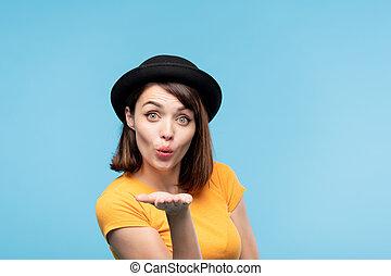 Flirty brunette girl in black hat sending you air kiss while...