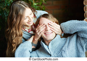Flirty play - Young woman closing man eyes by her palms