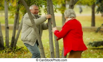 Playful senior couple chasing each other in the park, embracing and waving at the camera afterwards