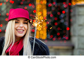 Flirty smiling blonde model wearing fashionable winter outfit, having fun with sparklers at the bokeh background. Space for text