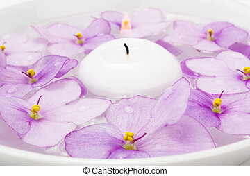 Floating candle in water and lilac flower
