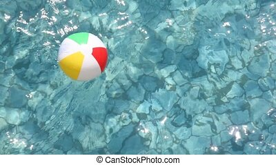 floating colour children\'s ball in waving water in swimming...