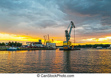 A large floating crane in the harbor at sunset. Gdansk, Poland.