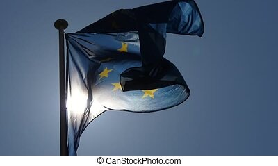 Exciting view of a waving European Union flag with a blue background and twelve yellow stars flying at a nice sunset in slow motion.