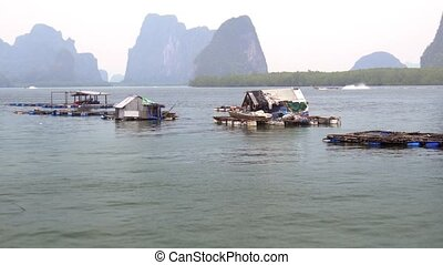 Floating fish cages, anchored near the remote, island fishing village on Koh Panyee, in southern Thailand. 4k footage