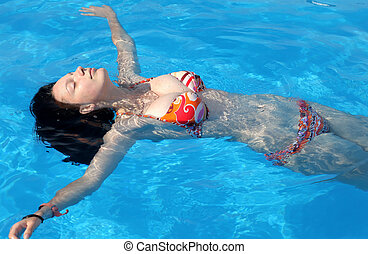 Floating girl at swimming pool