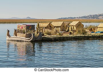 View of floating island Uros, Lake Titicaca, Peru, Bolivia and reed boat with its reflection.