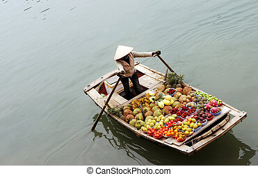 Floating market - Woman selling fruit from a boat on Halong ...