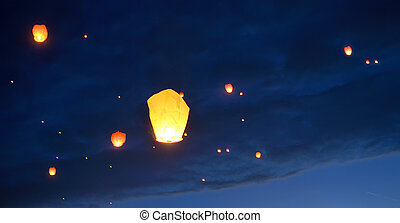 Floating paper lanterns on night sky