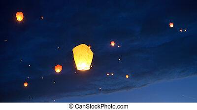 Floating paper lanterns on night sky