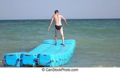 Floating platform at sea - Man on a plastic floating...