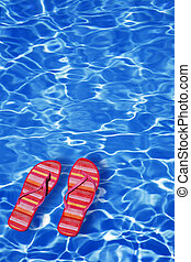 Floating Shoes - Bright blue pool water background with...