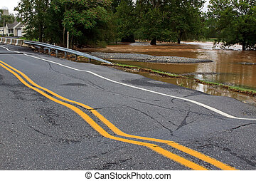 A rural road and bridge severely damaged by heavy flooding.