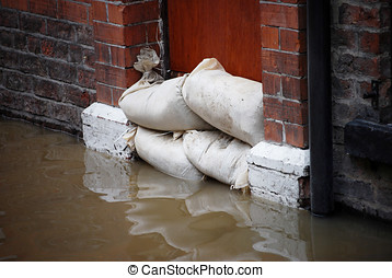 Flood defences - Sandbag barrier in doorway of flooded...
