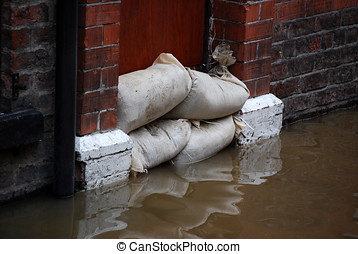 Flood defences - Sandbag barrier in doorway of flooded...